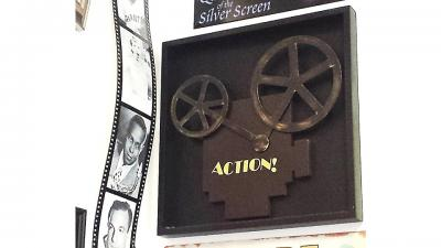 "Image of film reel and black camera silhouette that says ""action"""