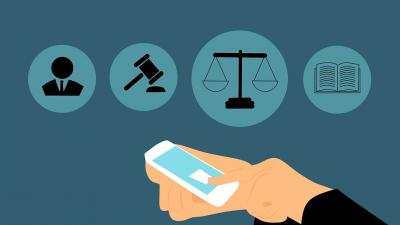 Hands holding a phone with symbols for an attorney, a gavel, scales, and a book in the background