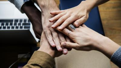 Image of hands on top of each other to symbolize cooperation